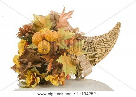 Thanksgiving cornucopia, wicker horn of plenty, centerpiece with fake flowers, leaves