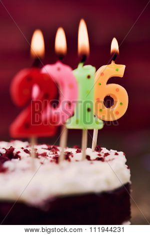 closeup of four lit number-shaped candles of different colors forming the number 2016, as the new year, on a cake