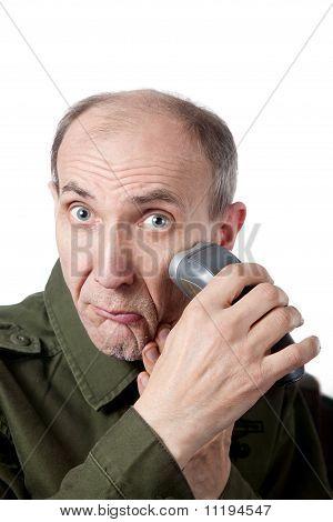 Anciano, afeitarse la barba con afeitadora aislado en blanco