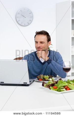 Handsome Man Looking At His Laptop While Having Lunch
