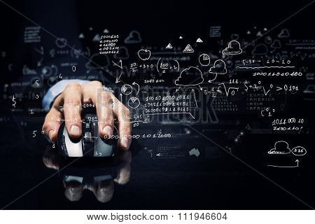 Hand of businessman in suit on dark background using wireless computer mouse