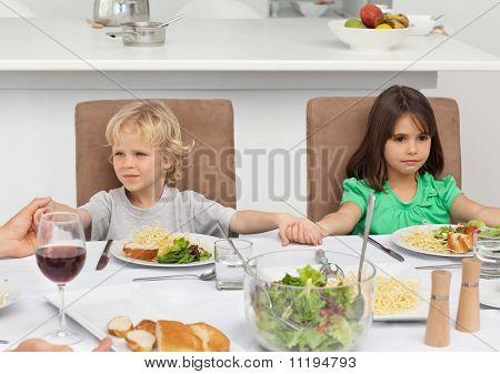 Irmão e irmã, segurando suas mãos rezando na hora do almoço