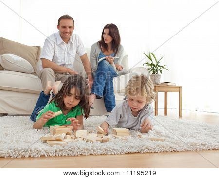 Happy Parents On The Sofa Looking At Their Children Playing On The Floor
