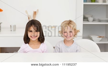 Lovely Brother And Sister Sitting At A Table In The Kitchen
