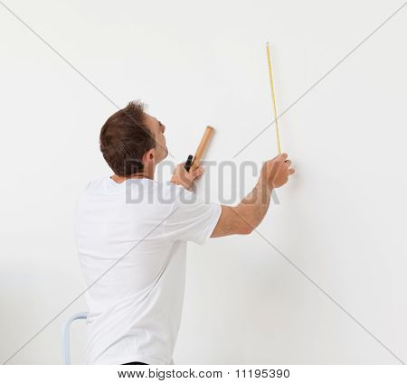 Handsome Man Looking At A Wall With Ruler And Tools