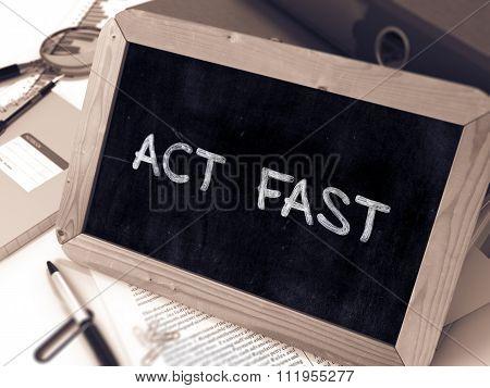 Act Fast Handwritten by white Chalk on a Blackboard.
