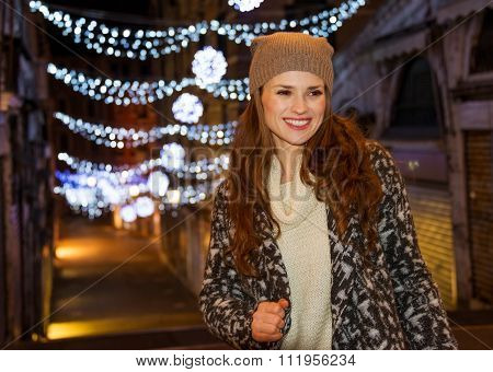 Stylishly Dressed Woman Standing In Front Of Christmas Lights