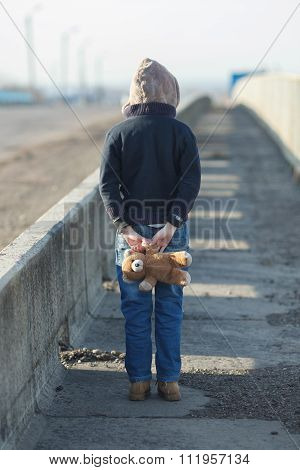 Little Homeless Boy Holding A Teddy Bear