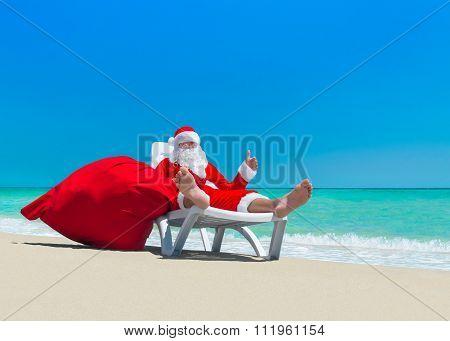 Santa Claus With Christmas Sack On Deckchair At Ocean Beach