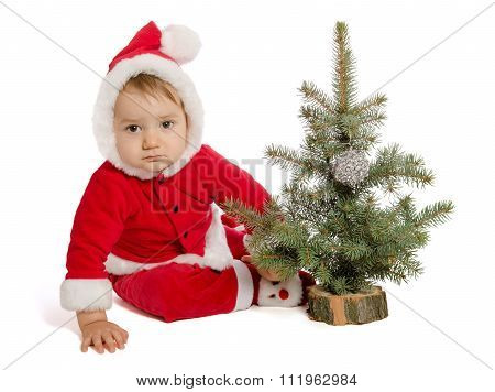 Sad Baby In Santa Claus Clothes With Xmas Tree On White Background