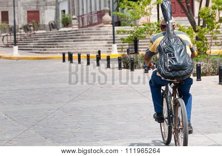 Man with guitar backback and hat on bicycle bike in the street of Granada