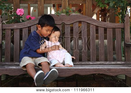 Japanese brother and sister (5 years old boy and 0 year old girl) sitting on the bench