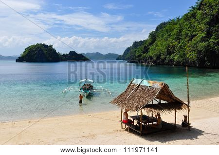 Bald Man pulling wooden traditional filipino boat while two women rest in bamboo hut at white sand b