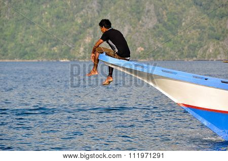 Man Sitting and relaxing in the front of a wooden boat