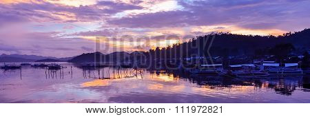 Pretty Pink orange Sky cloudscape over an island with reflection and wooden traditional filipino boa