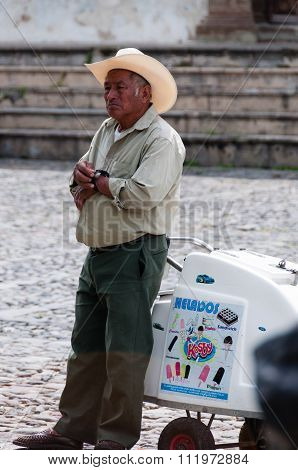 Man with cowboy hat Leaning On An Ice cream Cart on the street