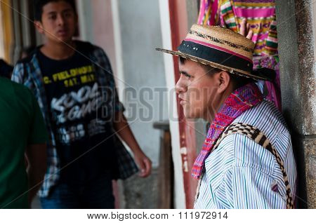 Man Wearing A Native Hat Leaning on a Cemented Pillar