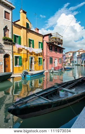 VENICE, ITALY - 17 OCTOBER 2015: Typical street scene in Burano, near Venice, Italy with vivid its colorful brightly painted houses and a canal with a fishing boat. Venice, Italy on 17 October 2015.