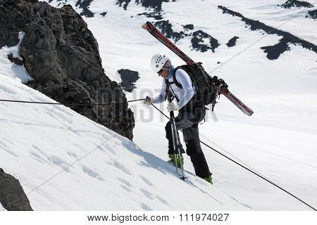 Ski Mountaineer Rises On The Rock On A Rope With Skis Strapped To A Backpack