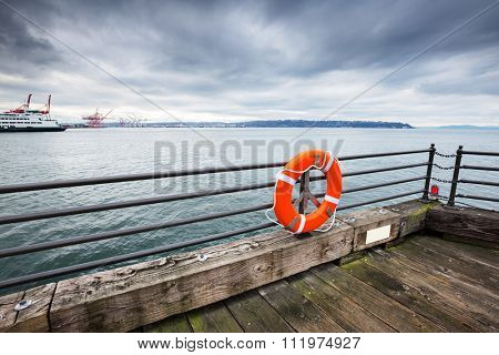 liner on the sea and water on view of empty old wooden floor with orange buoy on waterfront railing in cloudy sky