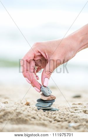 Hand Placing Stone On The Pyramid On Sand. Sea In The Background