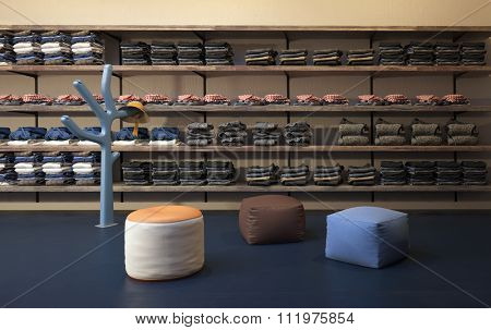 Interior of Upscale Clothing Store with Plush Ottomans, Hat Rack and Clothing Neatly Stacked on Wall Shelves. 3d Rendering.
