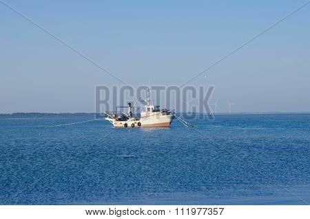 Fishing Boat In The Estuary In The Background Of Wind Turbines