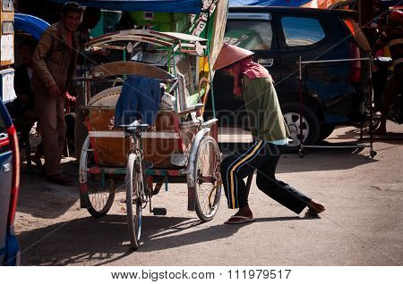 Man with hat Pumping Air Into The Wheel of his tricycle
