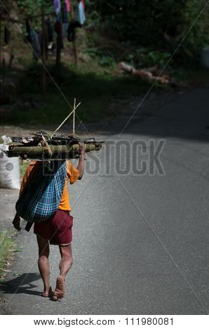 Lonely Asian Man from behind walking Barefoot on the street carrying log wood