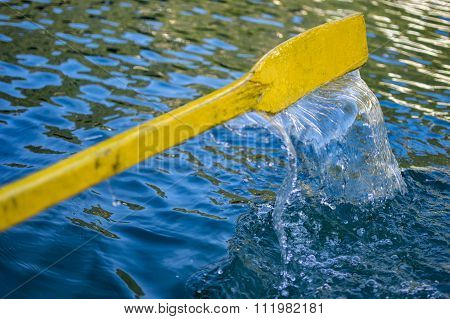 Yellow Oar Of Boat In Dark Water