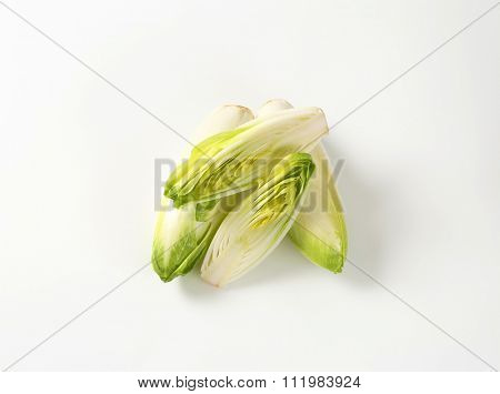 whole and halved heads of fresh belgian endive