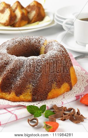 close up of marble bundt cake and cup of coffee