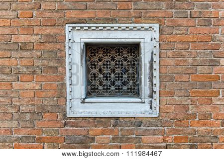 Square small window with white frame and decorative metallic grid on a brick wall of an old building, architectural detail