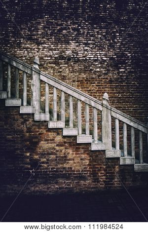 Old external staircase on a red brick building with heavy vignetting around the sides and an ominous ambiance, highlight to the centre on the steps