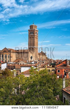 Skyline view of the Basilica dei Frari, Venice, Italy with its square campanile dominating the surrounding rooftops against a sunny blue sky