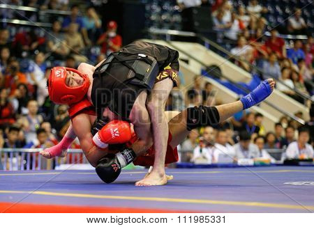 JAKARTA, INDONESIA - NOVEMBER 18, 2015: Kun Zhang of China (red) fights Ali Abdulkhalikov of Russia (black) in the men's 75kg Sanda final event at the 13th World Wushu Championship 2015.