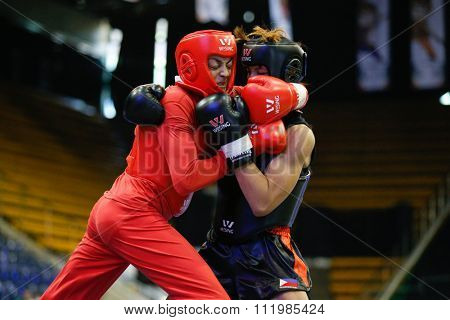 JAKARTA, INDONESIA - NOVEMBER 18, 2015: Shahrbano Semiromi of Iran (red) fights Hergie Bacyadan of Philippines (black) in the women's 65kg Sanda final event at the 13th World Wushu Championship 2015.