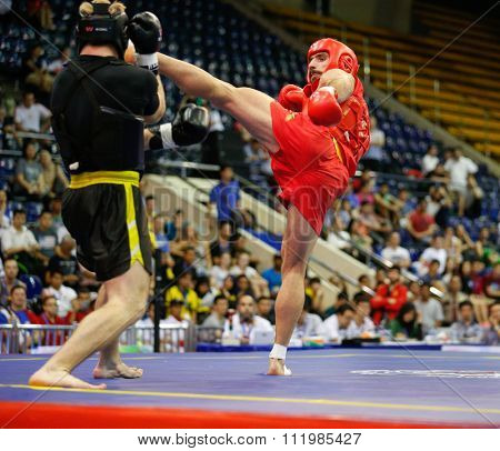 JAKARTA, INDONESIA - NOVEMBER 18, 2015: Amir Fazli of Iran (red) fights Dmytro Batok of Ukraine (black) in the men's 85kg Sanda final event at the 13th World Wushu Championship 2015.