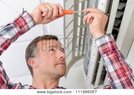 Man repairing an air conditioning unit
