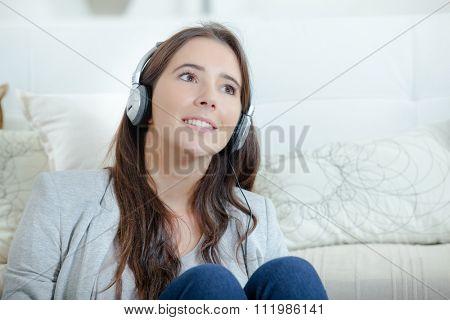 girl listening to headphones, sat on floor