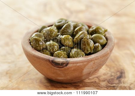 marinated capers in olive bowl on wood table