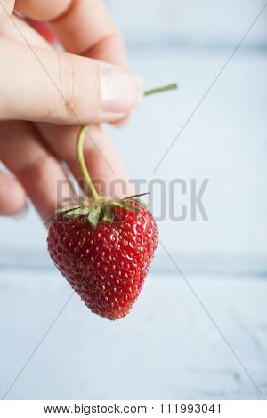 Strawberry being picked up by the stem