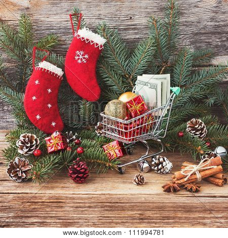 Christmas Gifts And Money In Small Shopping Trolley, Wooden Background And Christmas Decoration. Ton