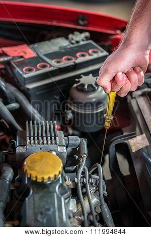 Car mechanic in auto repair service checking oil