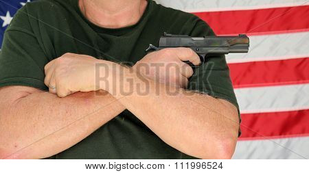 An unidentifiable person holds a loaded, and cocked pistol across his chest with an American flag background behind him. 2nd amendment rights. self protection. security of life and property.