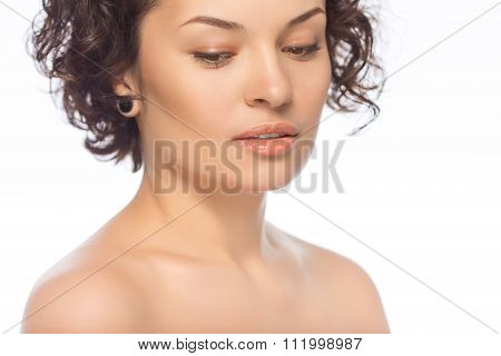 Young attractive woman looks downwards.