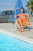Young Woman In Orange Bikini And Pareo Sitting On Beach Chair poster