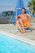 Young Woman In Orange Bikini And Pareo Sitting On Beach Chair poster