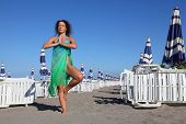 Beautiful Young Woman In Blue Swimsuit And Pareo Stands On Beach, Rows Of White Deck Chairs poster
