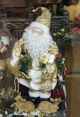 santa claus exposed with two smaller santa claus in a small shop. poster